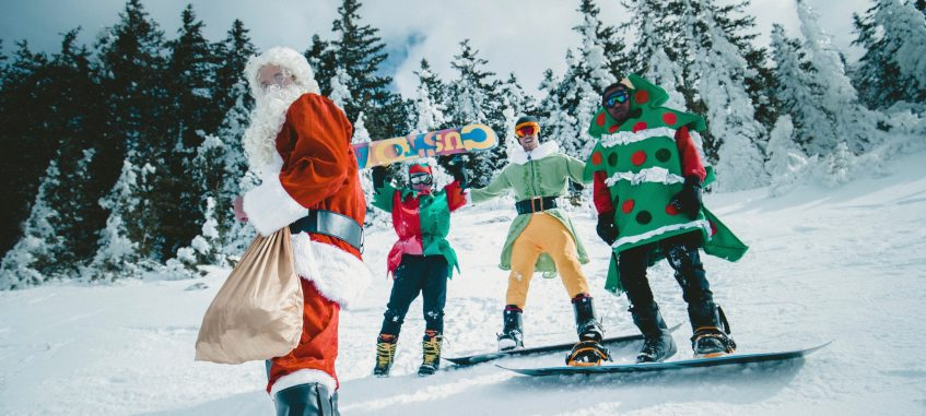 santa claus with elves ride snowboards