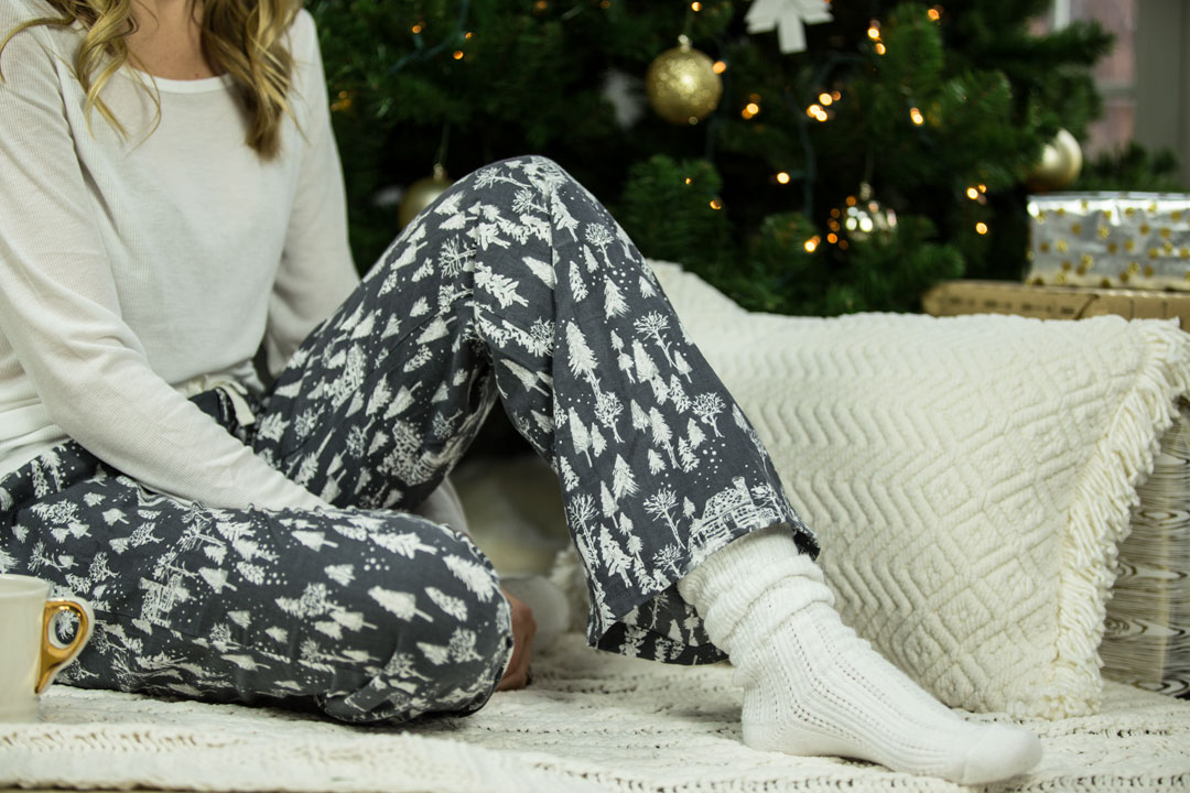 a blond girl in pajamas and socks is sitting on the sofa