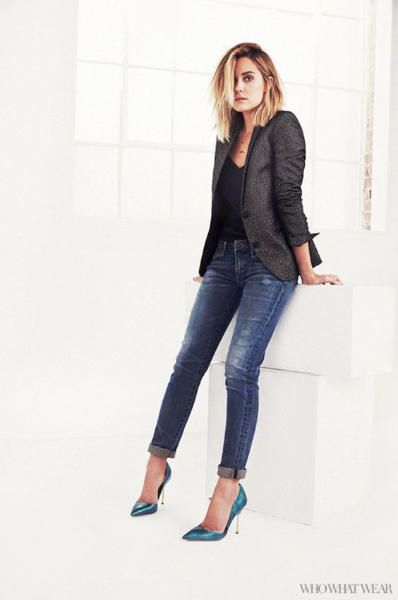 a blond girl wearing jeans, black top and a greay blazer