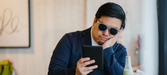 a bored guy in sunglasses making staring at phone screen