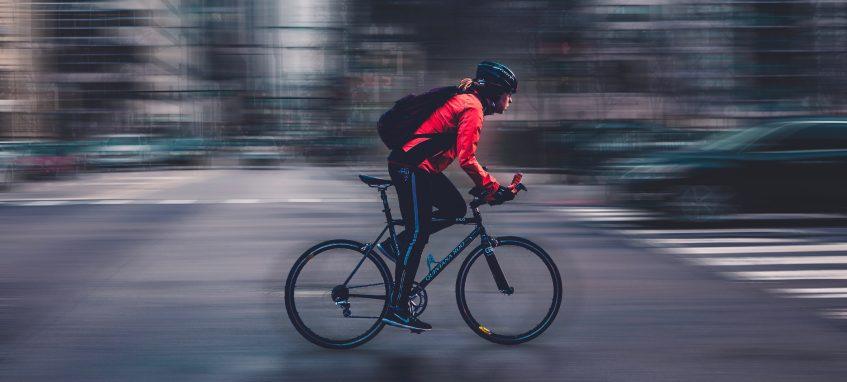 a boy rides bike fast in the big city