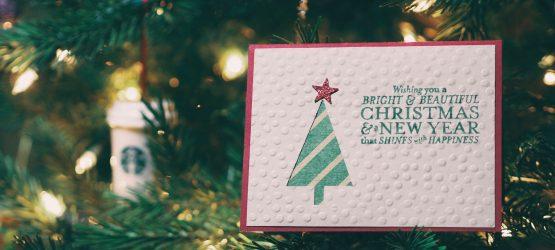 a christmas card hanging on christmas tree