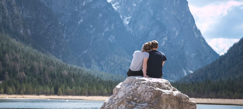a college couple admiring mountain rocks at the lake