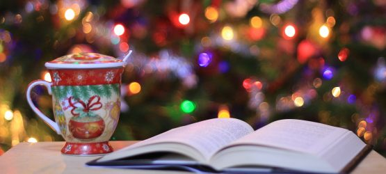 a decorated mug and a book with a christmas tree in the background