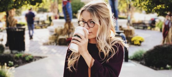 a girl drinking a cup of coffee from Starbucks