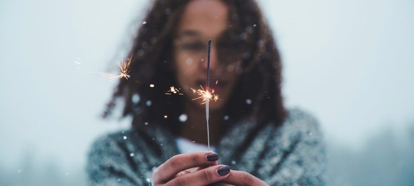 a girl holding a sparkler in her hands