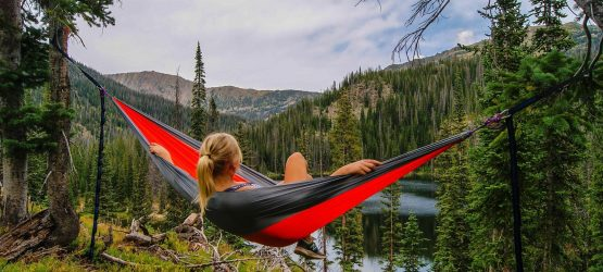 a girl is lying in a hammock admiring the mountains