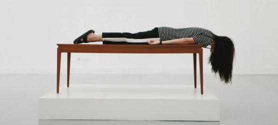 a girl lying on the table looking down the floor in a white room