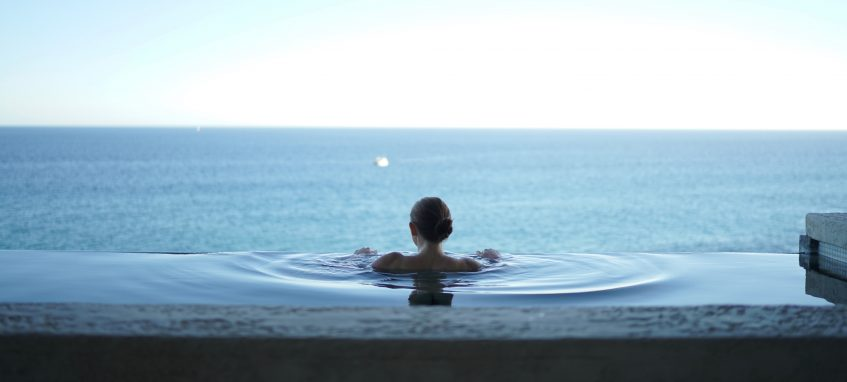 a girl swimming in the pool looking at the sea