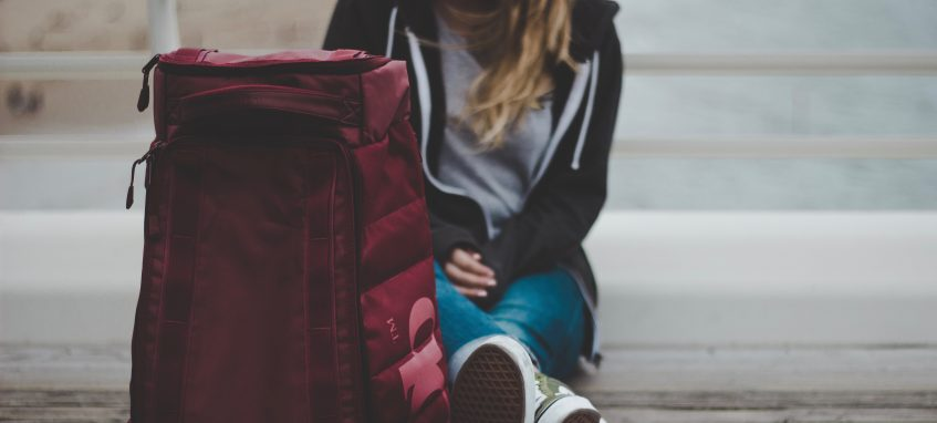 a girl with a backpack sitting on the ground