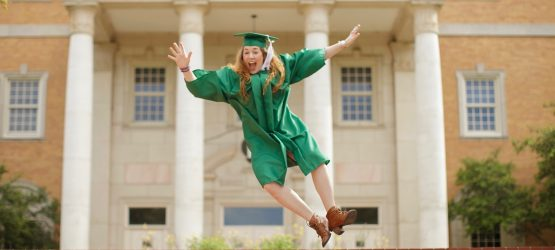 a graduate girl jumping up near the university