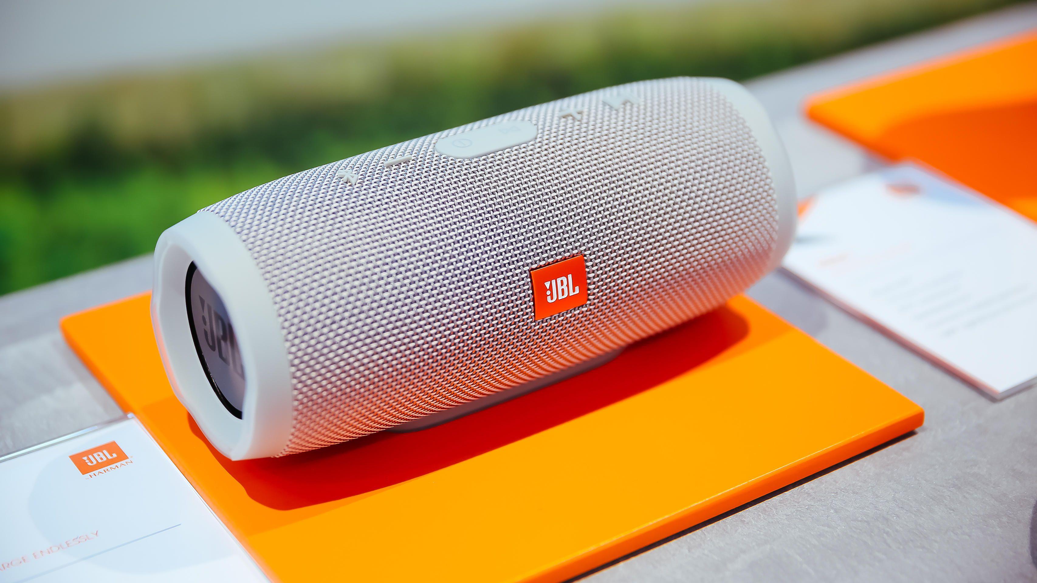 a grey bluetooth speaker on an orange mat