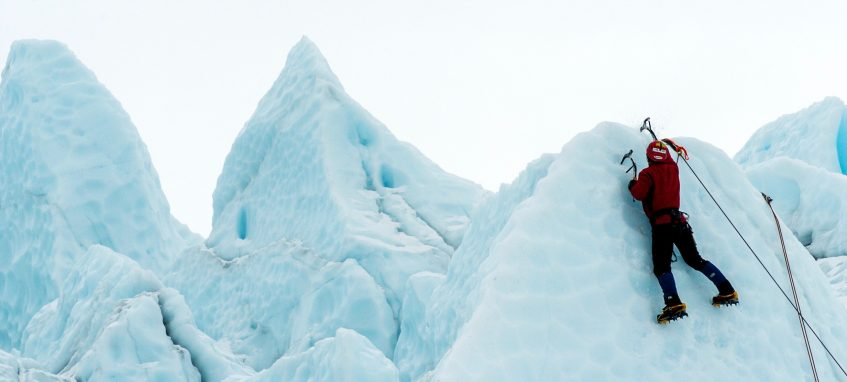 a guy climbing a mountain covered with ice