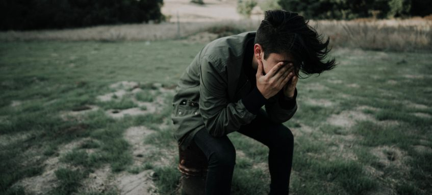 a guy holding his face in hands in despair