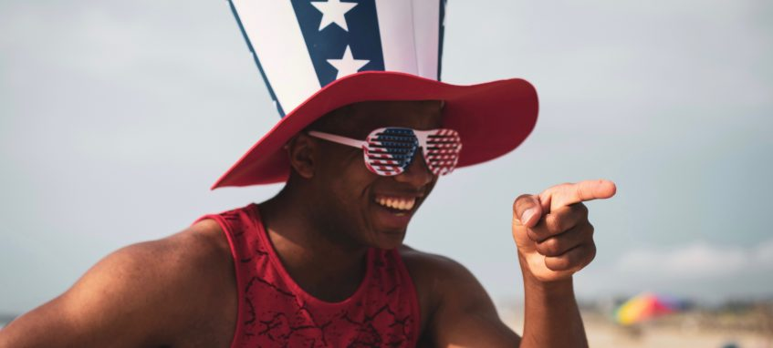 a guy in uncle Sam's hat is pointing at someone and laughing