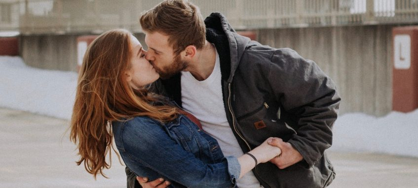 a guy kissing a girl on the roof