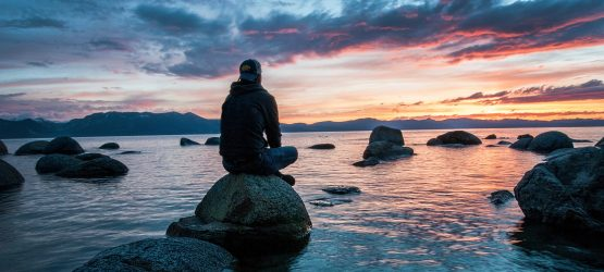 a guy sitting on the rock in the sea at sunset