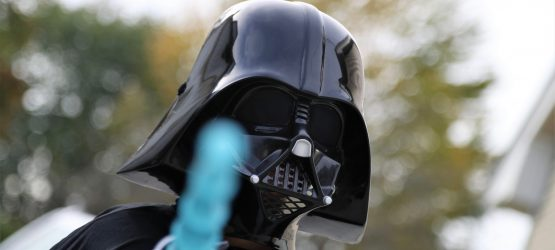 a guy wearing a darth vader mask holds a lightblaster