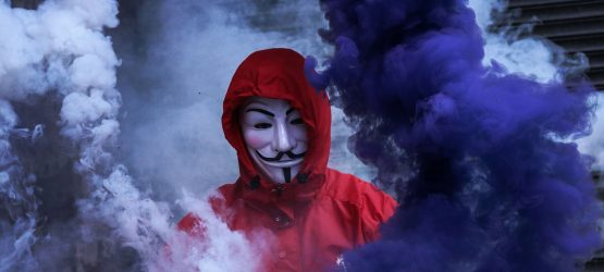 a guy wearing an anonymous mask stands in clouds of smoke
