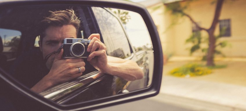 a man taking photo of his reflection in the car mirror