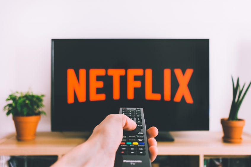 a person pointing a remote control towards the screen with a sign Netflix