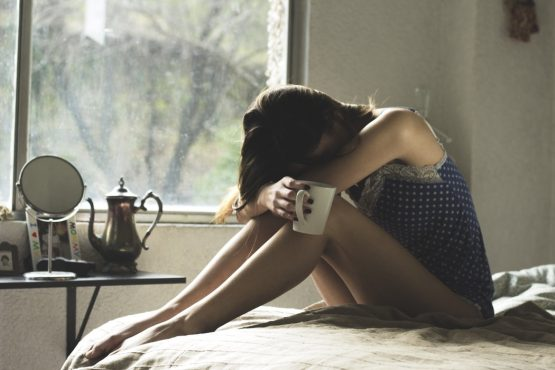 a depressed girl sitting on the bed with a cup of tea in her hands