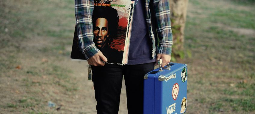 a student wearing a plaid shirt holds a briefcase and vinyl records