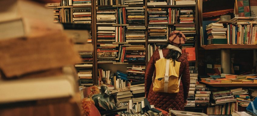 a student with a backpack standing in a library surronded by a pile of books