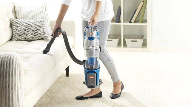 a woman using a portable vacuum cleaner in the living room