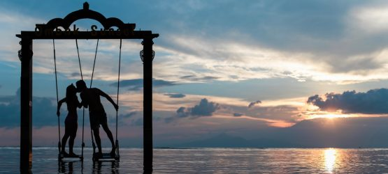 a young couple kissing on swings in the middle of the sea at sunset
