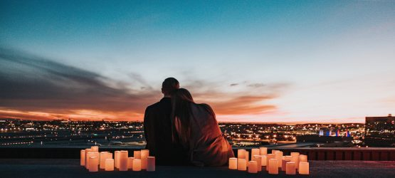 a young couple surrounded with candels looking at sunset