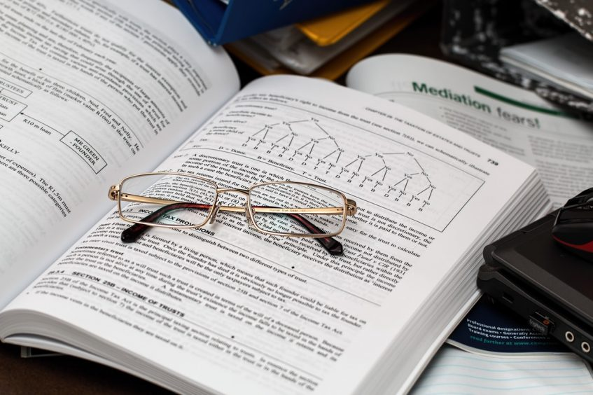 glasses lying on top of the opened book