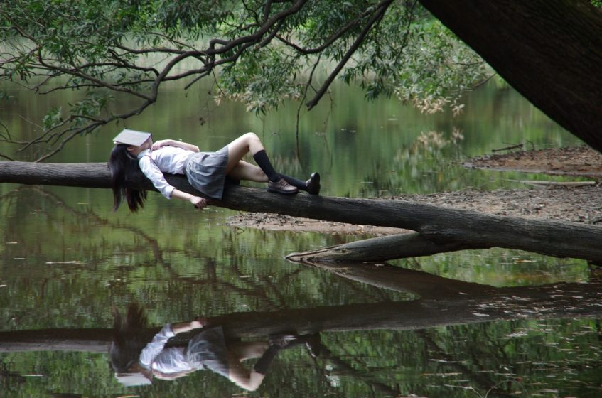 a girl lying near the river bank with a book on her face