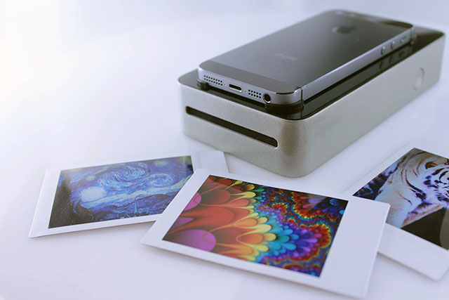 an instant photo portable printer with an iphone on it, and three colorful picters