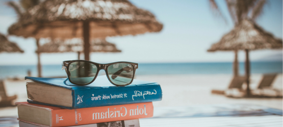 books and sunglasses the with the background of the beach