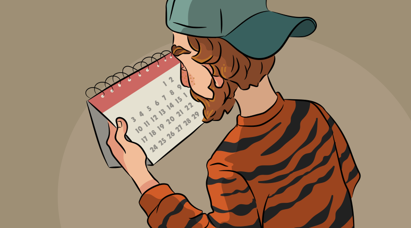 a guy in a tiger sweater looking at a calendar