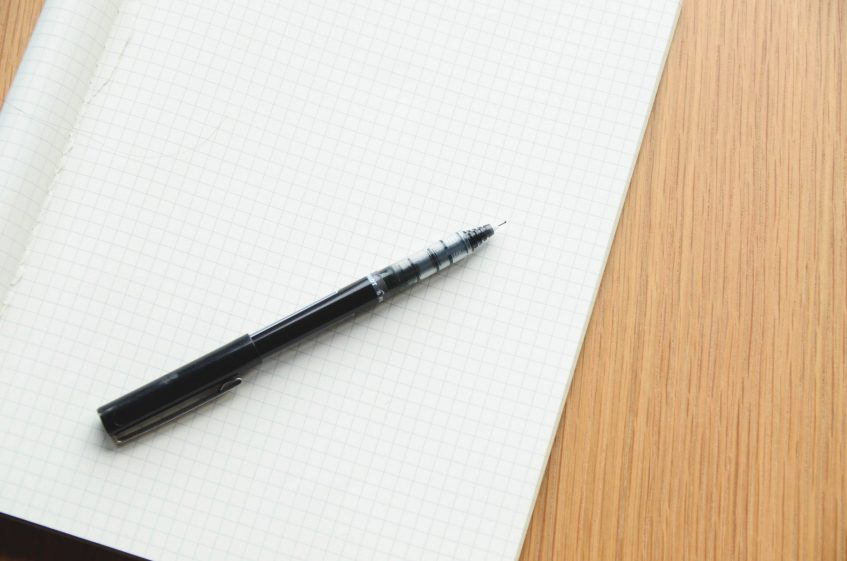 a blank notebook with a pen