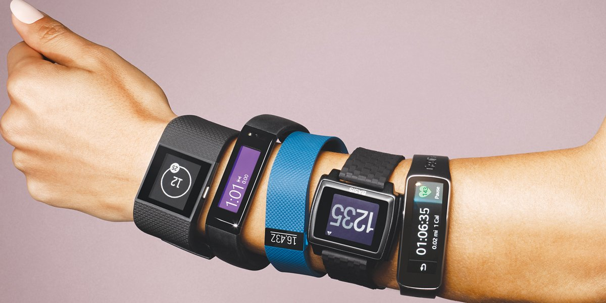 five fitness trackers of different types on one hand