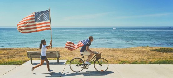 the girl with American flag is chasing the guy on bicycle wrapped with the flag of United States