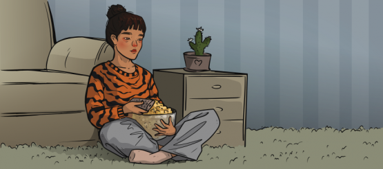 the girl in a tiger sweater is sitting with popcorn and a remote in hands