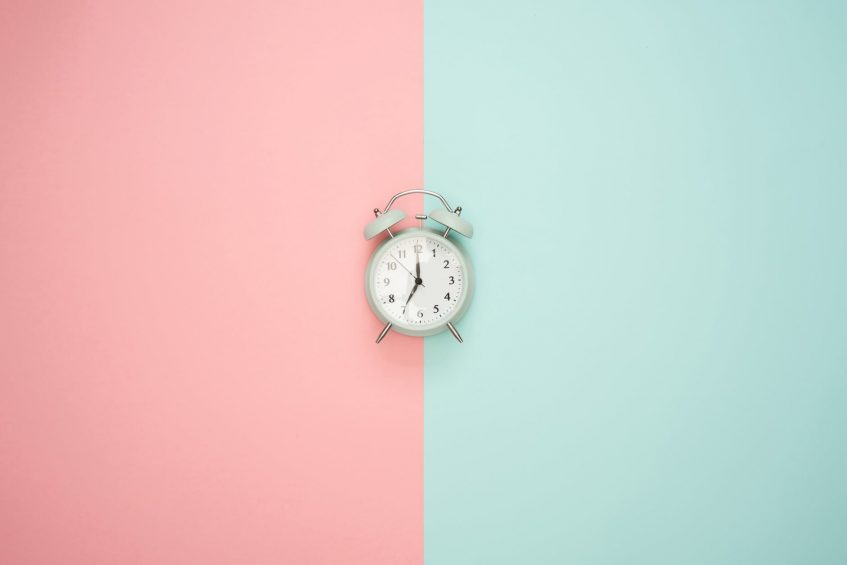 a clock on a pink and blue background