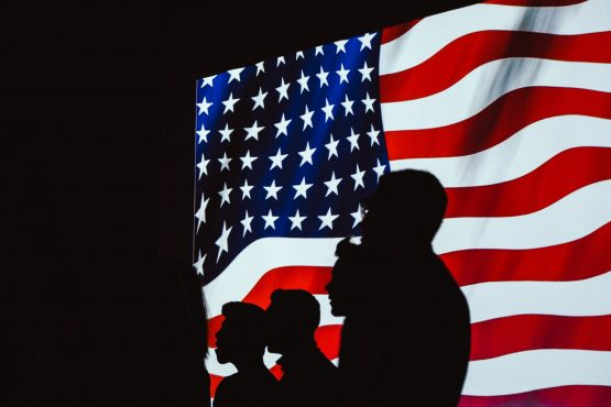 people with american flag on background