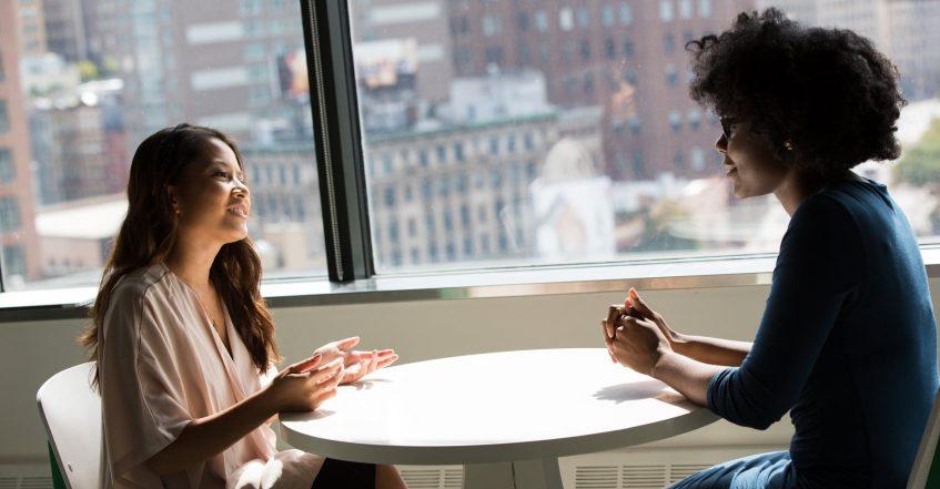 two girls talking next to video