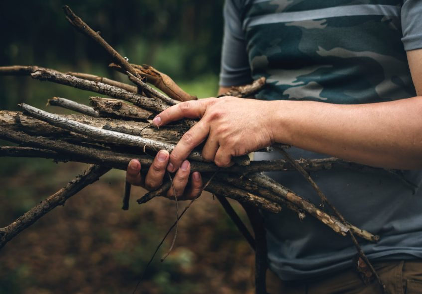 a guy holding a bunch of sticks
