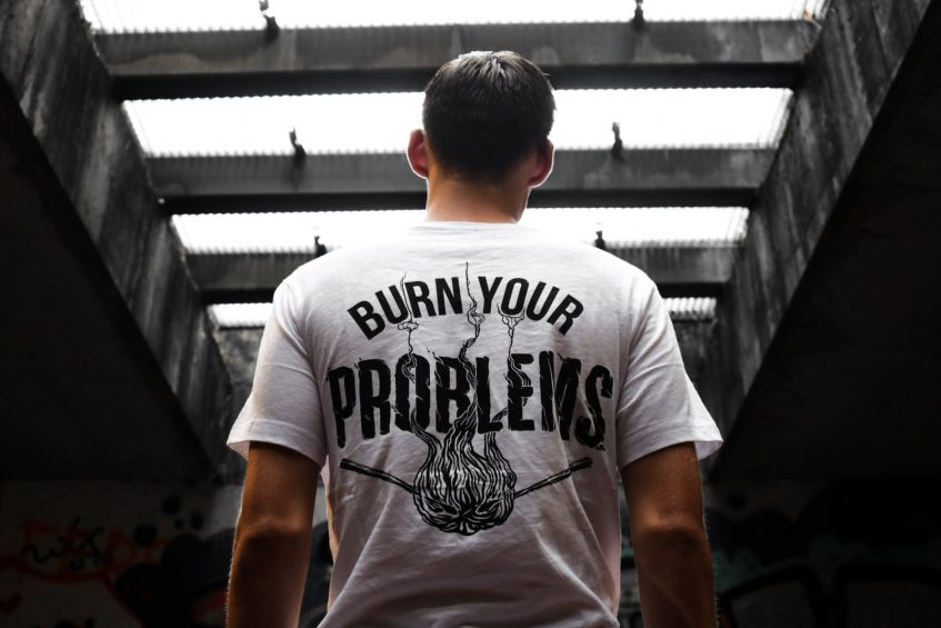 a guy wearing a t-shirt that says burn your problems