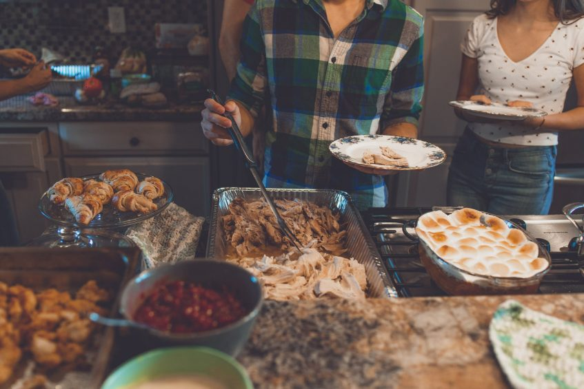 a guy standing next to table full of food