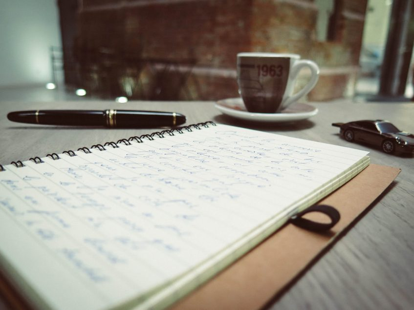 a notebook, a cup, and a pen on the table