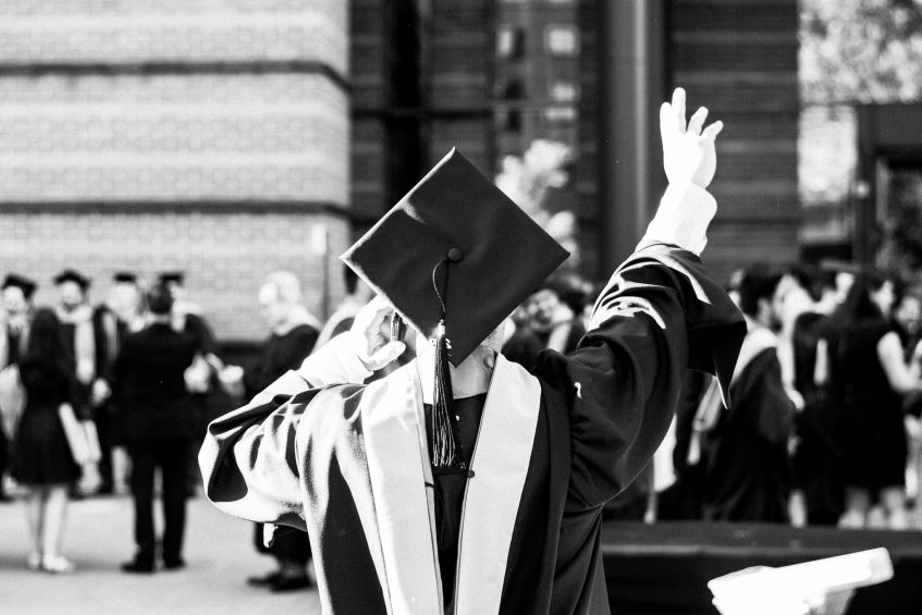 a graduation student waves at someone