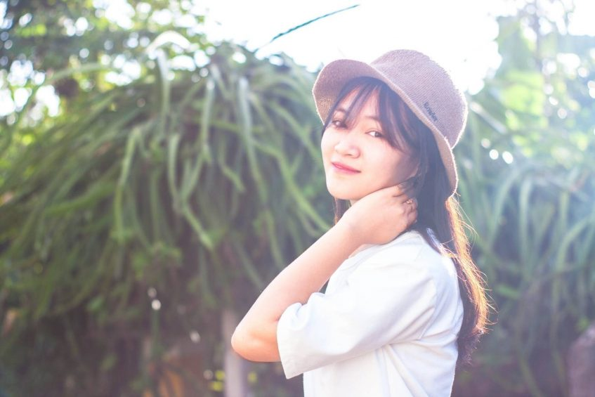 asian girl in a hat smiling in a summy day