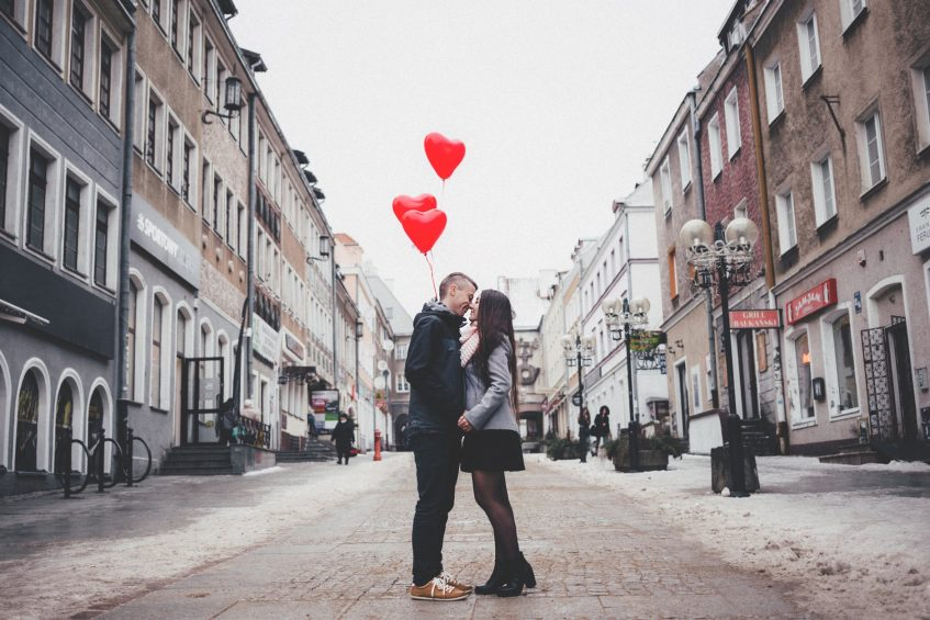 a couple standing in the middle of the street kissing with heart balloons in their hands